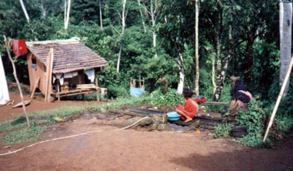 A Dibabawon woman washes clothes near the hose. This is where they also wash dishes and take a bath. Water comes from a nearby river.